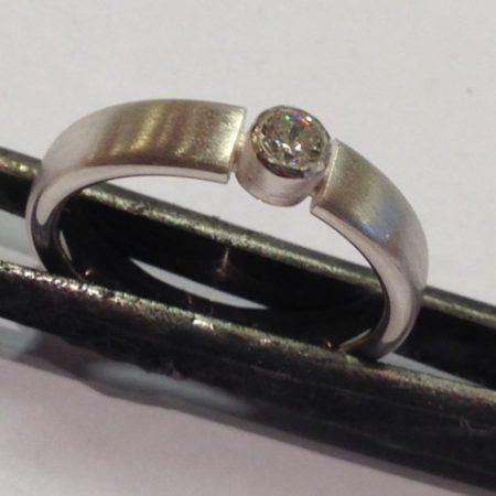 Ring met as in het kastje van de steen. Hierdoor lijkt de steen donkerder