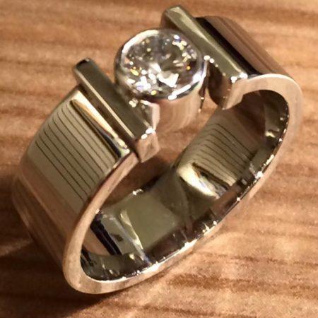 Strakke witgouden ring met as onder de steen