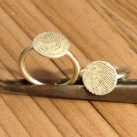 Twee fijne ringen met rond plaatje met vingerafdruk gemaakt door goudsmid