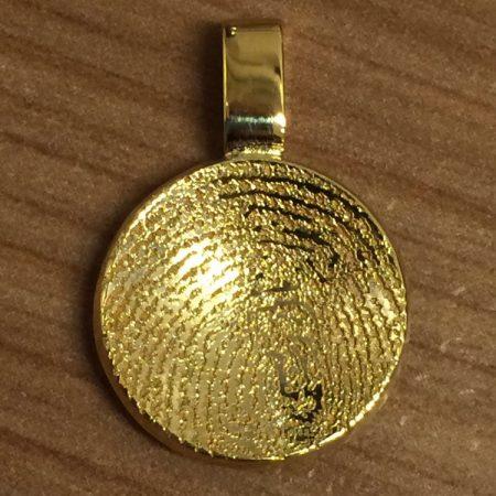Gouden ronde hanger met vingerafdruk. Eenvoudig en sierlijk.