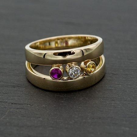 van-twee-gouden-trouwringen-een-ring-gemaakt-met-gekleurde-steentjes