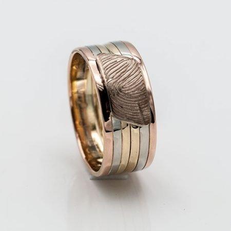 Van twee trouwringen met drie kleuren een ring met vingerafdruk gemaakt